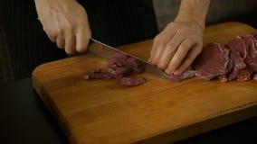 Homem que corta tiras longas da carne vermelha filme