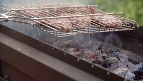 Homem que cozinha a carne no assado O homem frita a carne no fogo em uma estrutura A carne é fritada em um fogo barbecue grade filme