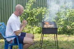 Homem que cozinha a carne no assado Pares novos que fazem o assado em seu jardim Homem que cozinha a carne no assado imagens de stock
