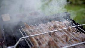 Homem que cozinha a carne O homem frita a carne no fogo em uma estrutura A carne é fritada em um fogo barbecue vídeos de arquivo