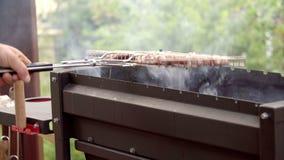 Homem que cozinha a carne O homem frita a carne no fogo em uma estrutura A carne é fritada em um fogo barbecue grade video estoque