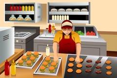 Homem que cozinha hamburgueres Fotografia de Stock Royalty Free