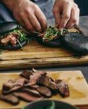 Homem que cozinha o fim grelhado hamburgueres da placa de madeira da carne acima foto de stock royalty free
