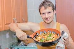 Homem que cozinha o paella Imagens de Stock