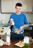 Homem que cozinha a omeleta Imagem de Stock