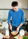 Homem que cozinha a omeleta com farinha Imagens de Stock Royalty Free