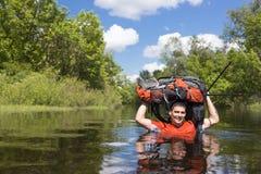 Homem que cruza o rio com uma trouxa fotografia de stock royalty free