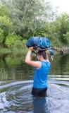 Homem que cruza o rio com uma trouxa fotos de stock