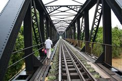 Homem que cruza uma ponte de estrada de ferro de aço fotografia de stock