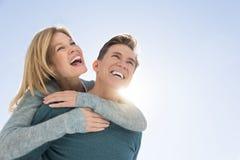 Homem que dá às cavalitas o passeio à mulher contra o céu claro fotos de stock royalty free