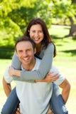 Homem que dá a esposa um sobreposto fotografia de stock royalty free