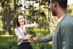 Homem que dá flores para sua amiga bonita imagem de stock