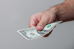 Homem que dá a nota de dólar Foto de Stock Royalty Free