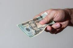 Homem que dá a nota de dólar vinte Fotografia de Stock Royalty Free