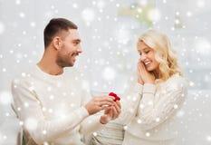 Homem que dá o anel de noivado da mulher para o Natal Imagens de Stock Royalty Free