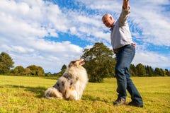 Homem que dá o comando a seu cão Fotografia de Stock Royalty Free