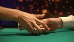 Homem que dá o dinheiro fêmea, efervescência das luzes no fundo, jogos ilegais do casino vídeos de arquivo