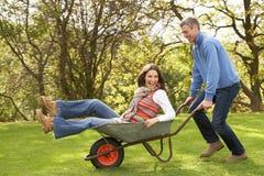 Homem que dá o passeio da mulher no Wheelbarrow Imagens de Stock Royalty Free