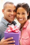 Homem que dá o presente à mulher fotografia de stock