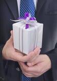 Homem que dá o presente Fotografia de Stock