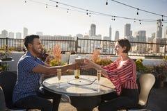 Homem que dá o presente da mulher como comemoram no terraço do telhado com skyline da cidade no fundo fotografia de stock royalty free