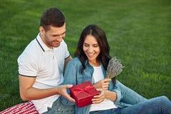 Homem que dá o presente das flores e da caixa de presente a sua amiga fotografia de stock royalty free