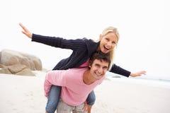 Homem que dá o sobreposto da mulher na praia do inverno Fotos de Stock