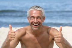 Homem que dá os polegares acima na praia fotos de stock royalty free
