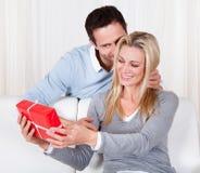 Homem que dá a sua esposa um presente da surpresa Fotografia de Stock Royalty Free