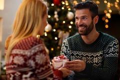 Homem que dá a surpresa do Natal à mulher foto de stock