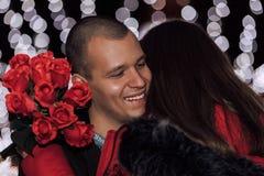 Homem que dá um ramalhete das rosas de sua amiga fotos de stock royalty free