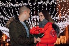 Homem que dá um ramalhete das rosas de sua amiga na noite imagem de stock