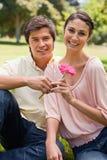 Homem que dá uma flor a uma mulher Foto de Stock Royalty Free