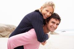 Homem que dá o sobreposto da mulher na praia do inverno Fotos de Stock Royalty Free