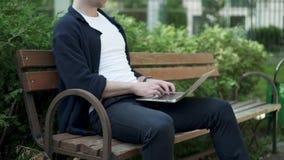 homem que datilografa no portátil que senta-se no banco mo lento video estoque