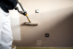 Homem que decora paredes com pintura Pintura do trabalhador do emplastro da construção e renovação com ferramentas profissionais foto de stock