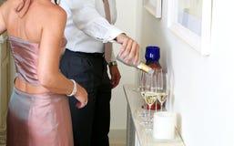 Homem que derrama Champagne em um partido de jantar Fotos de Stock Royalty Free