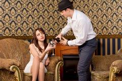 Homem que derrama sua amiga algum vinho Foto de Stock Royalty Free