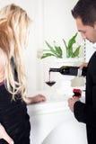 Homem que derrama um vidro do vinho tinto Imagem de Stock