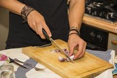 Homem que desbasta a cebola vermelha com a faca afiada na cozinha Imagens de Stock