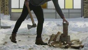Homem que desbasta a madeira no movimento lento da vila do inverno da jarda da neve vídeos de arquivo