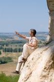 Homem que descansa na rocha da montanha Imagens de Stock Royalty Free