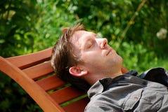 Homem que descansa no jardim Imagens de Stock