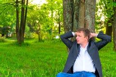 homem que descansa perto de uma árvore alta imagem de stock