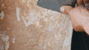 Homem que descasca o papel de parede velho com espátula especial Papel de parede amarelo, decrépito na parede, fim do reparo da c video estoque