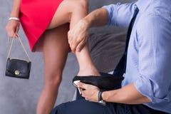 Homem que descola a sapata 'sexy' do ` s da mulher imagem de stock