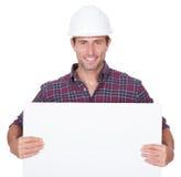 Homem que desgasta o cartaz da terra arrendada do chapéu duro foto de stock royalty free