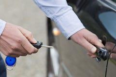 Homem que destrava a porta de carro. fotografia de stock