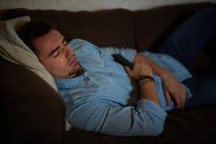 Homem que dorme com a tevê girada sobre fotografia de stock royalty free