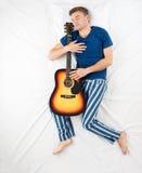 Homem que dorme com uma guitarra Fotos de Stock